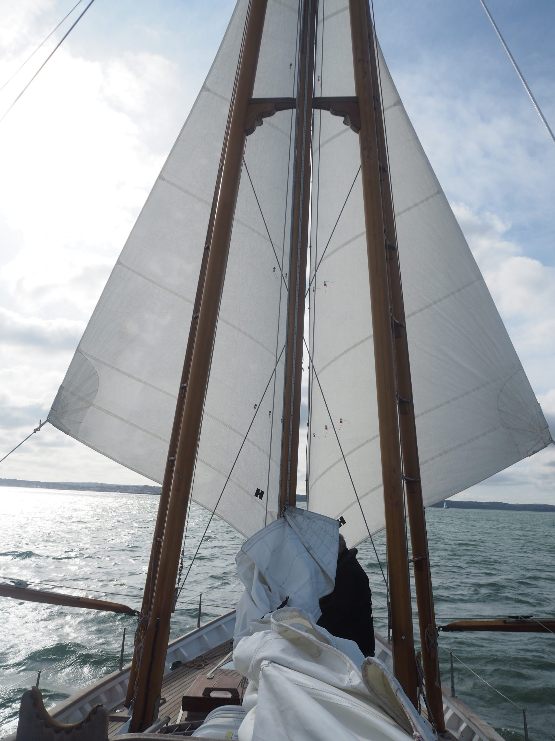 Boleh heading downwind, sporting her signature rig of boomed-out headsails and with a hint of sunshine ahead.